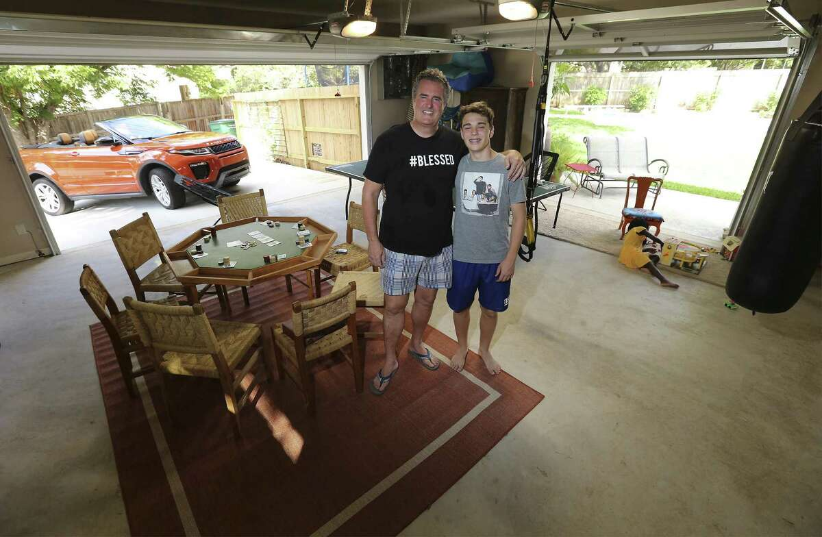 John Dunlap and his son, Jonah, pose for a photo as Dunlap's daughter, Emmy, plays in their second garage that has living space for a ping-pong table, poker table, workout area and also opens up to a new built-in pool in their backyard.