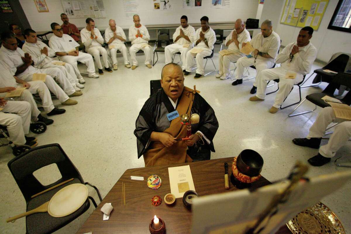 Myokei Cain-Barrett, center, a Buddhist priest from Houston leads a group of inmates from the Texas Department of Criminal Justice Navasota Unit during ministry services on Sunday, Oct. 11, 2009, in Navasota. Cain-Barrett holds service for the inmates once a week for about two hours and several of the inmates say that engaging with her is better than the prison psychologist.