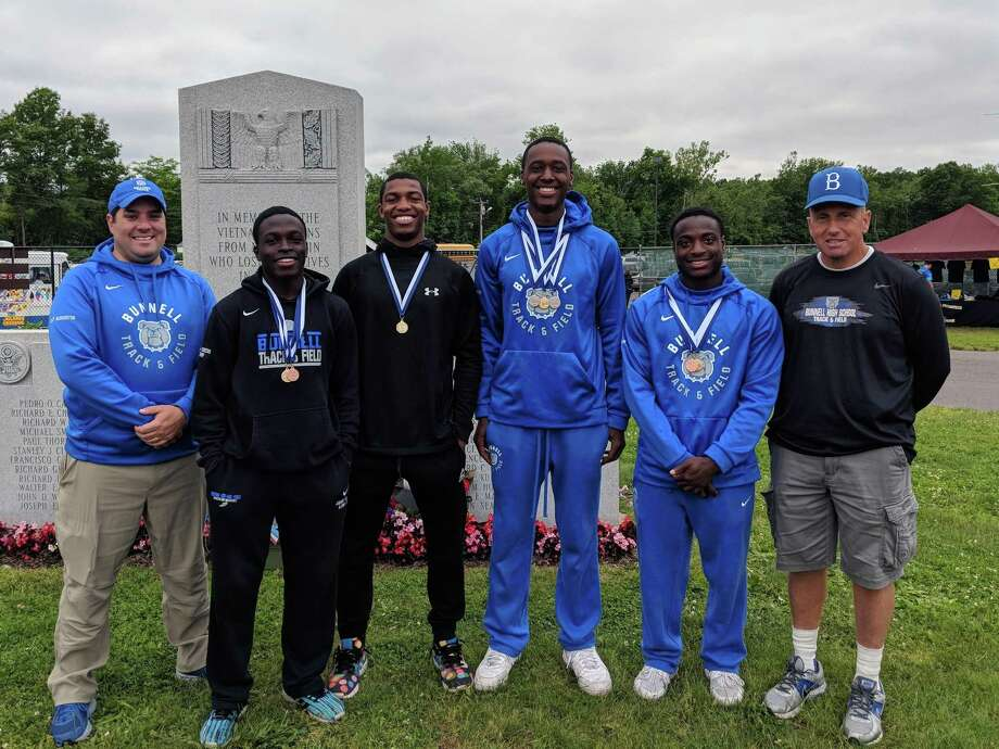 Bunnell assistant track coach Ryan Harrington, left, stands with the Bulldogs 4x100 Class MM state championship relay team: Jonathan Cineus, Ramsley Exantus, Elijah Henry and Christ N'Dabian. At far right is assistant coach Moe Scioletti. Photo: Contributed Photo / Contributed Photo / Stamford Advocate Contributed