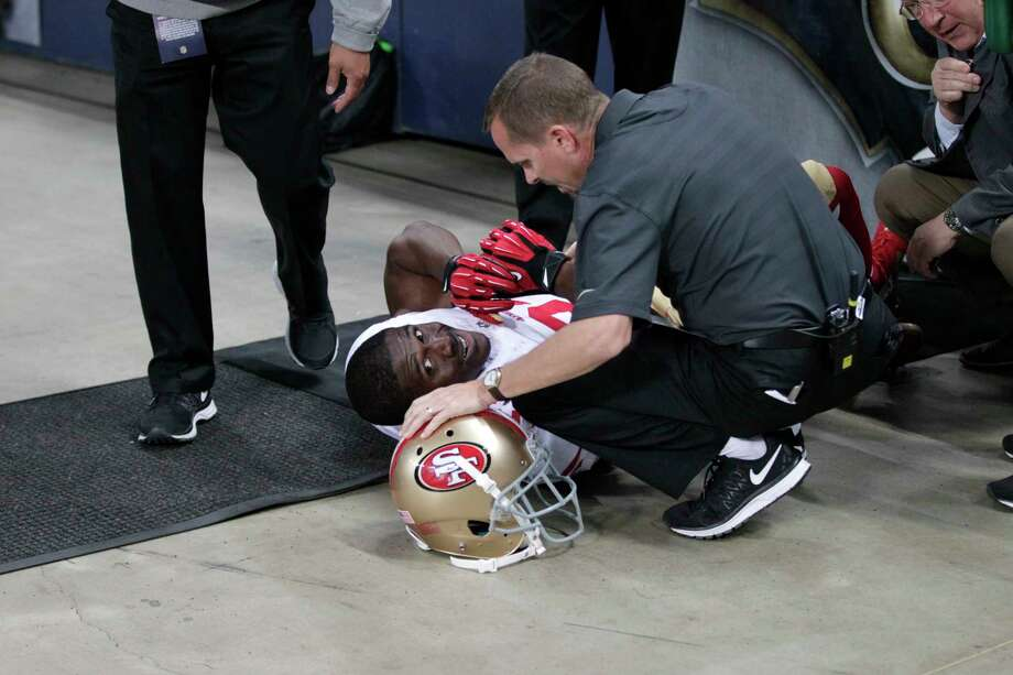 FILE - In this Nov. 1, 2015, file photo, San Francisco 49ers running back Reggie Bush is tended to by a trainer after slipping out of bounds after a running the ball during the first quarter of an NFL football game against the St. Louis Rams, in St. Louis. Former NFL running back Reggie Bush says dangerous conditions at a St. Louis stadium led to a season-ending injury in a case that could leave the city on the hook for damages, even though the Rams are long gone. The St. Louis Post-Dispatch reports that defendants in the civil trial, which began Tuesday, June 5, 2018, include two public entities. (AP Photo/Tom Gannam, File) Photo: Tom Gannam, Associated Press / FR45452 AP