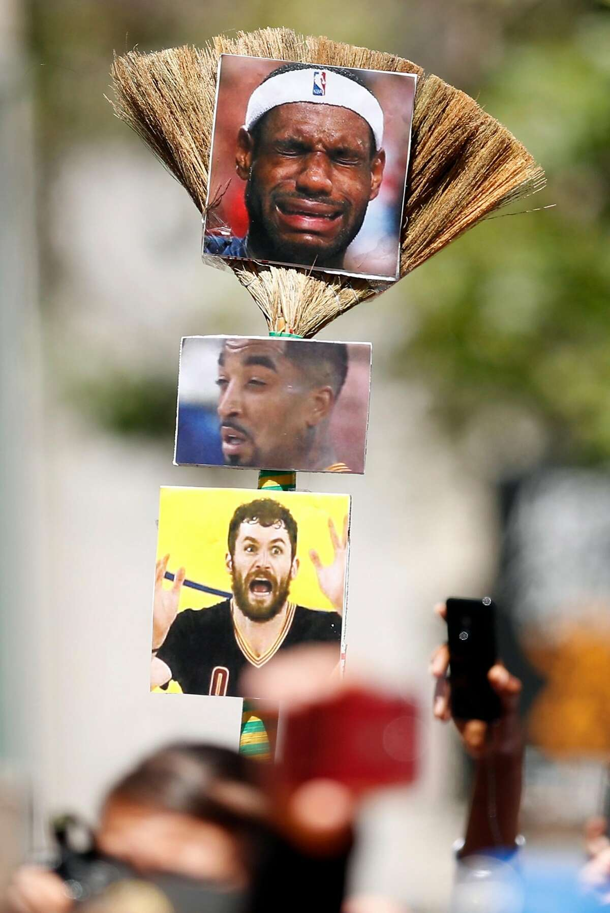A fan holds a broom with Cleveland Cavaliers' photos during Golden State Warriors' NBA Championship parade in Oakland, CA on Tuesday, June12, 2018.
