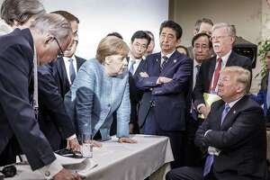 German Chancellor Angela Merkel — along with other world leaders — deliberates with President Donald Trump on the sidelines of the official agenda on the second day of the G7 summit on Saturday in Charlevoix, Canada.