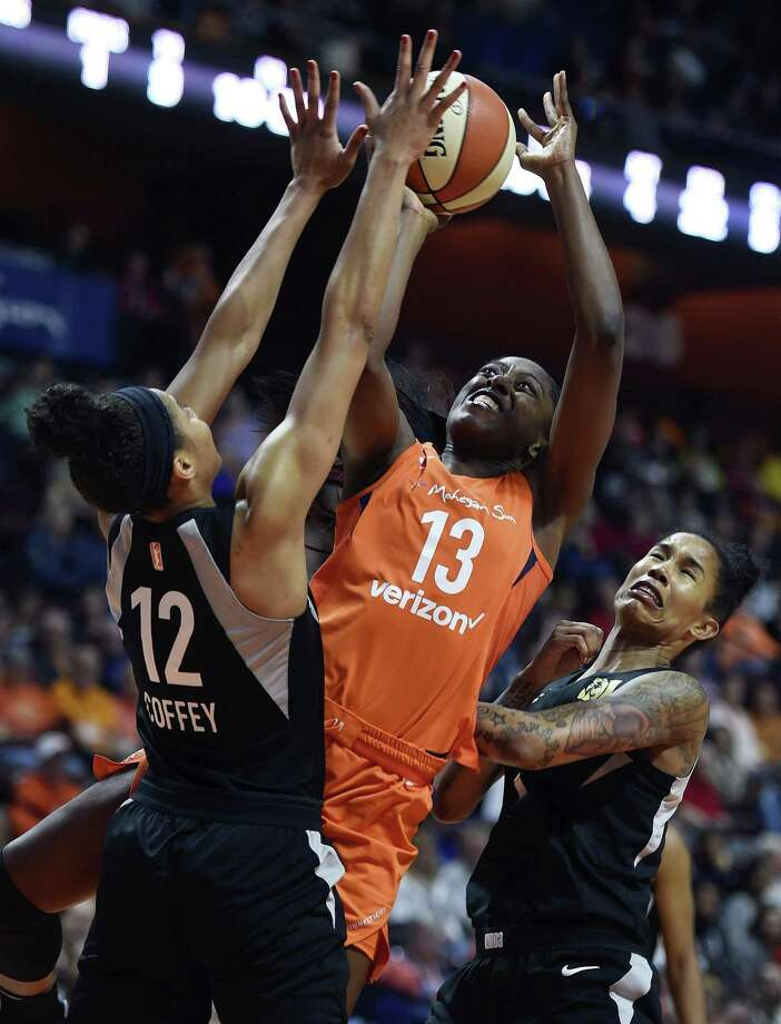 Connecticut Sun forward Chiney Ogwumike (13) draws the foul on the Las Vegas Aces' Nia Coffey (12) as Tamara Young, right, helps on defense in a May 20 game at Mohegan Sun Arena. Photo: Sean D. Elliot / Associated Press / 2018 The Day Publishing Company