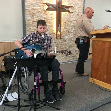 Kris Workman, 34, performs from his wheelchair at Sutherland Springs Baptist Church while the Rev. Frank Pomeroy, 52, wearing a Kimber 9mm pistol, stands at the pulpit on a recent Sunday morning. Workman was partially paralyzed during the Nov. 5 shooting. Pomeroy's 14-year-old daughter, Annabelle, was killed. The pastor is a strong supporter of gun rights and the Second Amendment, he has a Texas gun license, and he has worn a pistol for years. Photo: Pew Charitable Trusts