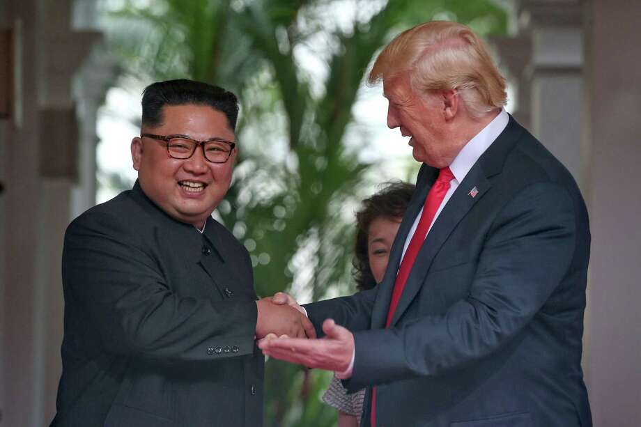 This handout photo taken on June 12, 2018 and released by The Straits Times shows North Korea's leader Kim Jong Un (L) shaking hands with US President Donald Trump (R) as they meet for the historic US-North Korea summit, at the Capella Hotel on Sentosa island in Singapore. Donald Trump and Kim Jong Un became on June 12 the first sitting US and North Korean leaders to meet, shake hands and negotiate to end a decades-old nuclear stand-off. Photo: KEVIN LIM / AFP /Getty Images / AFP
