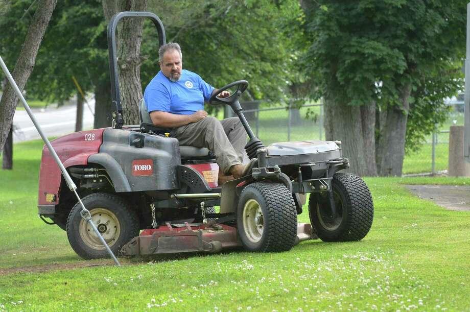 Tony Tuccinardi with Norwalk Parks and Recs cuts the grass around the softball field at Norwalk High School omn Monday June 11, 2018 in Norwalk Conn. Photo: Alex Von Kleydorff / Hearst Connecticut Media / Norwalk Hour