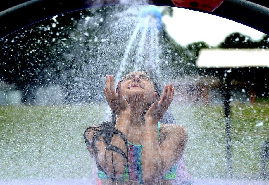 Gabriella Aguilar cools off beneath a misty spray while enjoying the Splash Park in Groves with family and friends Tuesday, June 12, 2018.  Kim Brent/The Enterprise Photo: Kim Brent / The Enterprise / BEN