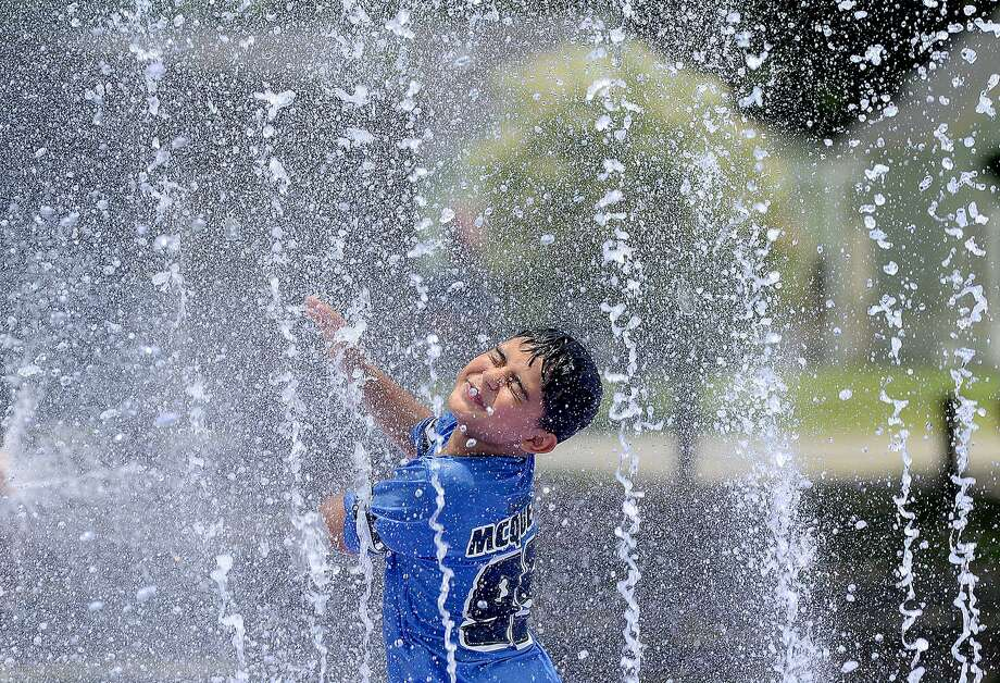 Estevan Cardenas reacts as he gets caught in a spray while enjoying the Splash Park in Groves with family and friends. Community pools and splash pads are the hot pick to cool off on Southeast Texas days now that school is out and summer is officially underway. Photo taken Tuesday, June 12, 2018 Kim Brent/The Enterprise Photo: Kim Brent / The Enterprise / BEN