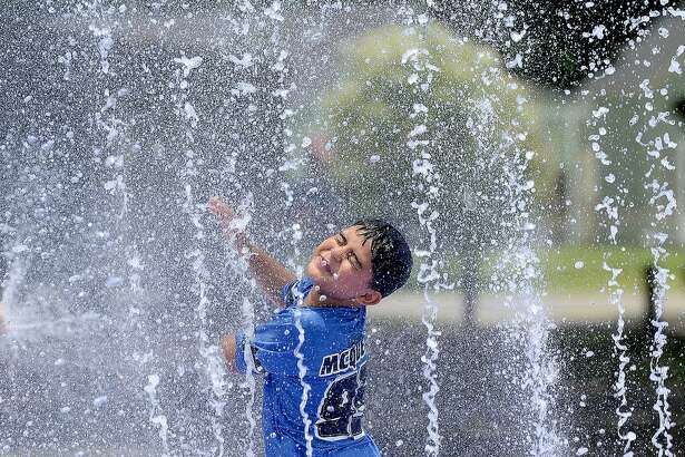 Estevan Cardenas reacts as he gets caught in a spray while enjoying the Splash Park in Groves with family and friends. Community pools and splash pads are the hot pick to cool off on Southeast Texas days now that school is out and summer is officially underway. Photo taken Tuesday, June 12, 2018 Kim Brent/The Enterprise