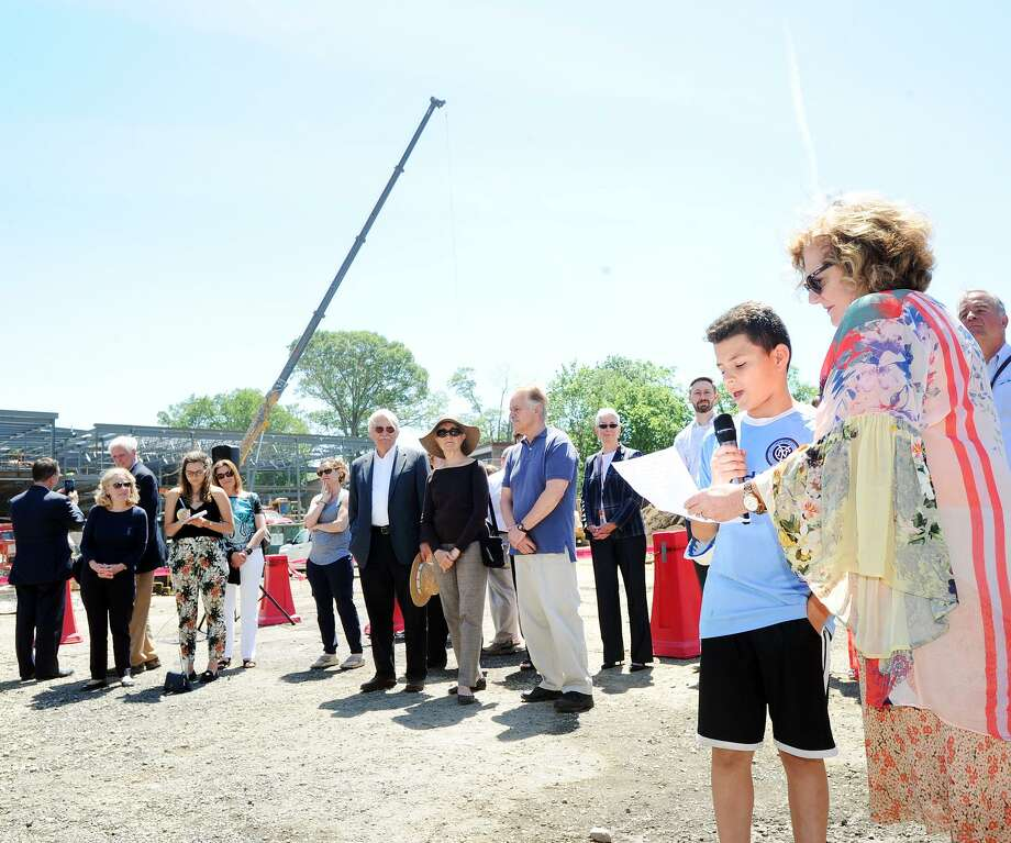 New Lebanon School Principal Barbara Riccio, right, stands by New Lebanon School fifth-grader Jacob Fajardo, 11, as Fajardo read a thank you note to all of those involved with the construction of the new New Lebanon School during the topping ceremony at the construction site of the new school in the Byram section of Greenwich, Conn., Tuesday, June 12, 2018. The final piece of structural steel was put in place by workers from the Gilbane Building Company. Photo: Bob Luckey Jr. / Hearst Connecticut Media / Greenwich Time