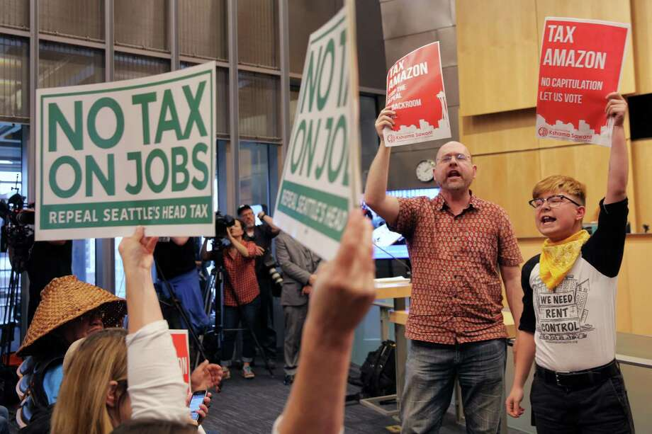 "Supporters and detractors of the ""head tax"" hold signs in council chambers during a City Council vote to repeal the tax on big businesses, which was voted for unanimously last month, Tuesday, June 12, 2018. Council voted 7-2 to repeal the tax. Photo: GENNA MARTIN, SEATTLEPI.COM / SEATTLEPI.COM"