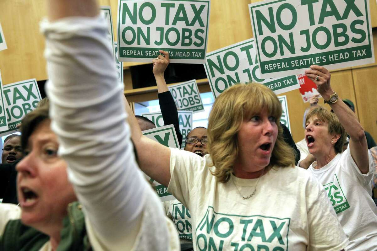 """Detractors of the """"head tax"""" hold signs in council chambers during a City Council vote to repeal the tax on big businesses, which was voted for unanimously last month, Tuesday, June 12, 2018. Council voted 7-2 to repeal the tax."""