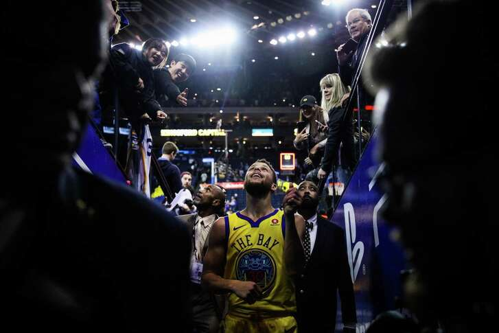 Stephen Curry (30) flicks his bracelet up into a crowd of fans after the Golden State Warriors defeated the Minnesota Timberwolves 126-113 at Oracle Arena in Oakland, Calif., on Thursday, January 25, 2018.