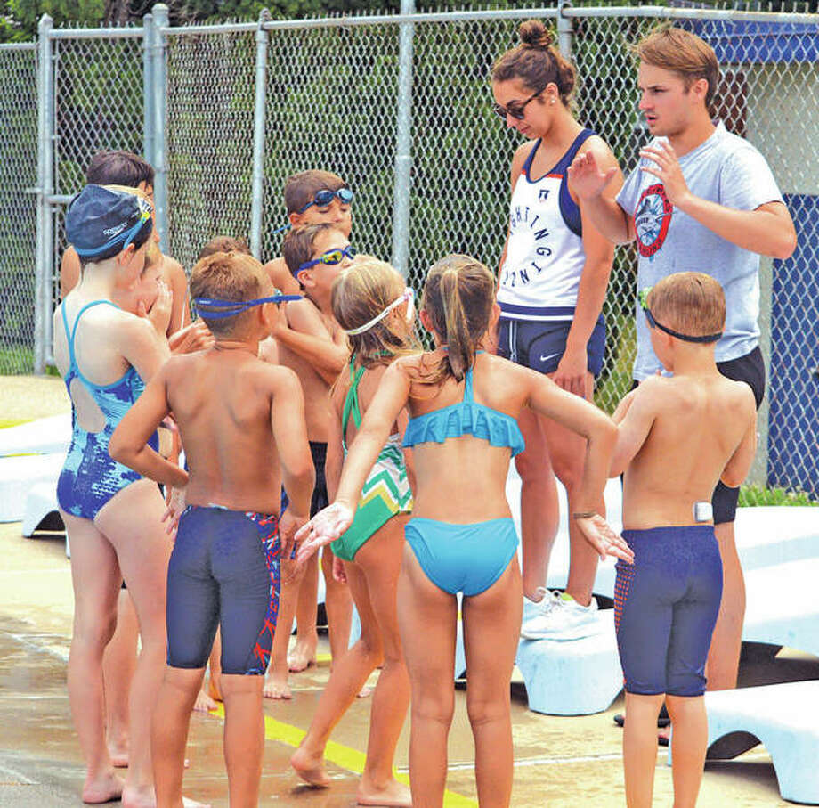 Water Works Marlins head coach Spencer Scholl, far right, and assistant coach Natalie Edwards give instructions to some members of the team at a Tuesday practice session. The Marlins open the SWISA season Thursday at Summers Port. Photo:       Scott Marion   For The Telegraph