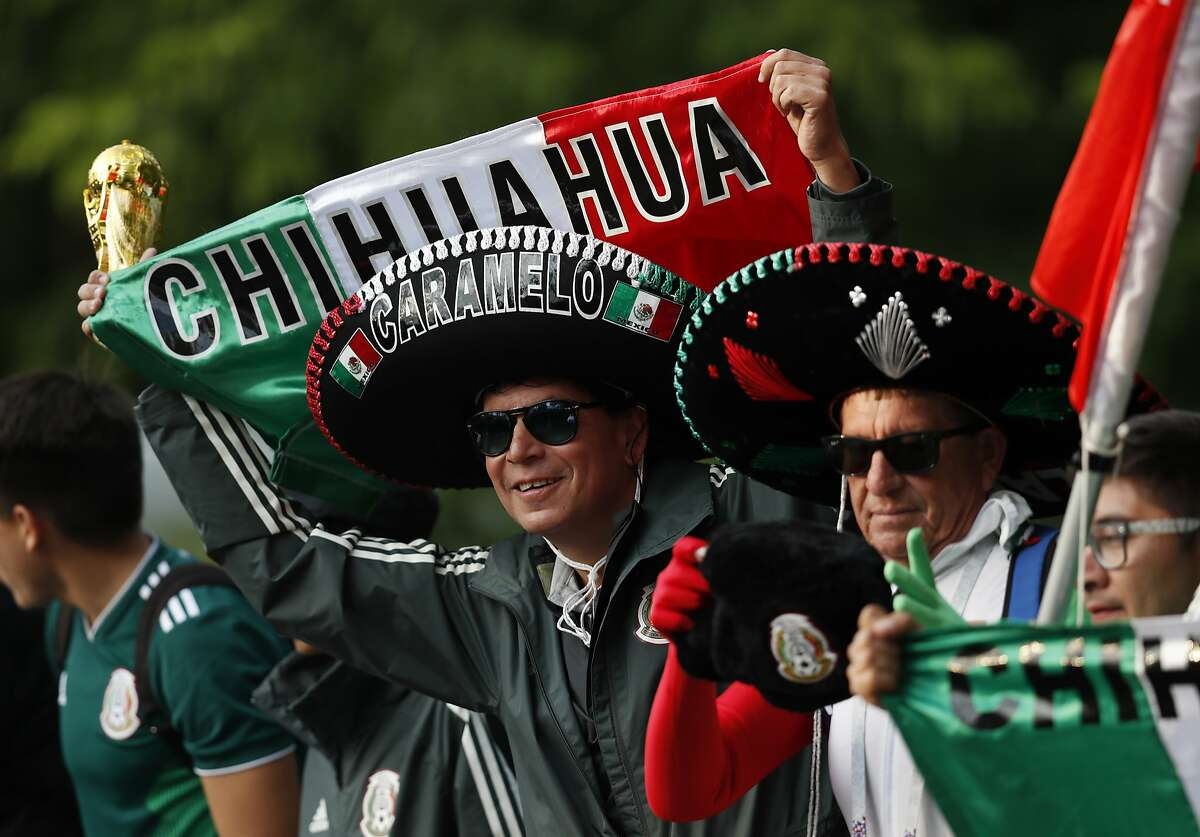 A Mexico fan wearing a tradition Mexican hat, cheers as his team, the Mexico national soccer team, boards a bus after training session at the 2018 soccer World Cup, in Moscow, Russia, Tuesday, June 12, 2018. (AP Photo/Eduardo Verdugo)