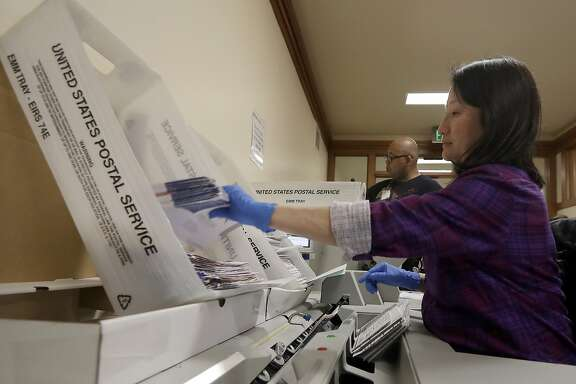 FILE - In this Friday, June 8, 2018, file photo, Mary Choi, right, and Mashaun De La Cruz extract ballots from envelopes at the Department of Elections in San Francisco. Election officials said approximately 42,000 ballots still needed to be counted. More than 208,000 ballots had been tallied by Saturday, June 9, 2018. (AP Photo/Jeff Chiu, File)