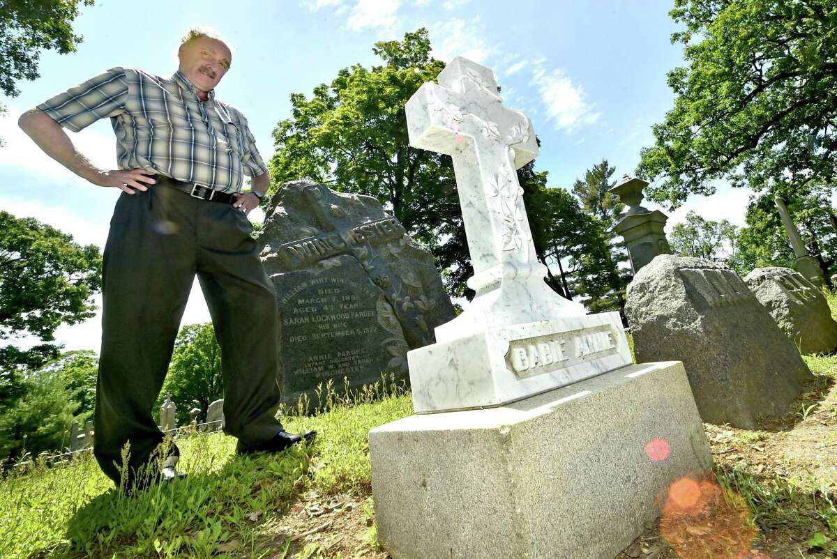 """Dale J. Fiore, general manager of the Evergreen Cemetery Association and Crematory in New Haven, next to the newly restored grave marker for """"Baby Annie"""" Winchester, granddaughter of the founder of Winchester Repeating Arms Co., Oliver Winchester."""