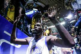 Golden State Warriors player Kevin Durant (35) high-fives fans in the tunnel after defeating the Cleveland Cavaliers in a game at Oracle Arena in Oakland, Calif., on Monday, Dec. 25, 2017.
