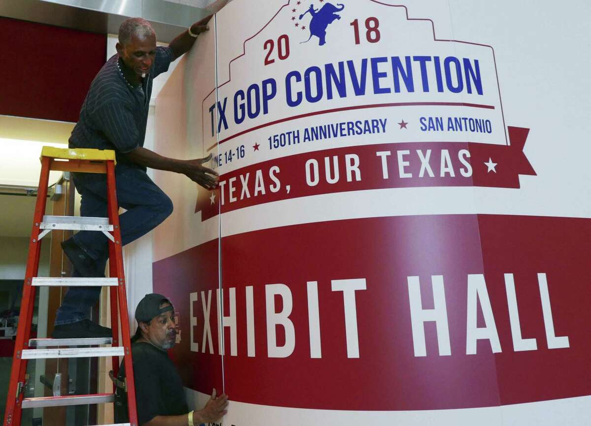Howard Satterwhite top, and Leonard Jimenez install a sign at the entrance to the convention hall in preparation for the opening of Republican Party of Texas state convention at the Henry B. Gonzalez convention center. The convention runs from June 14 through June 16.