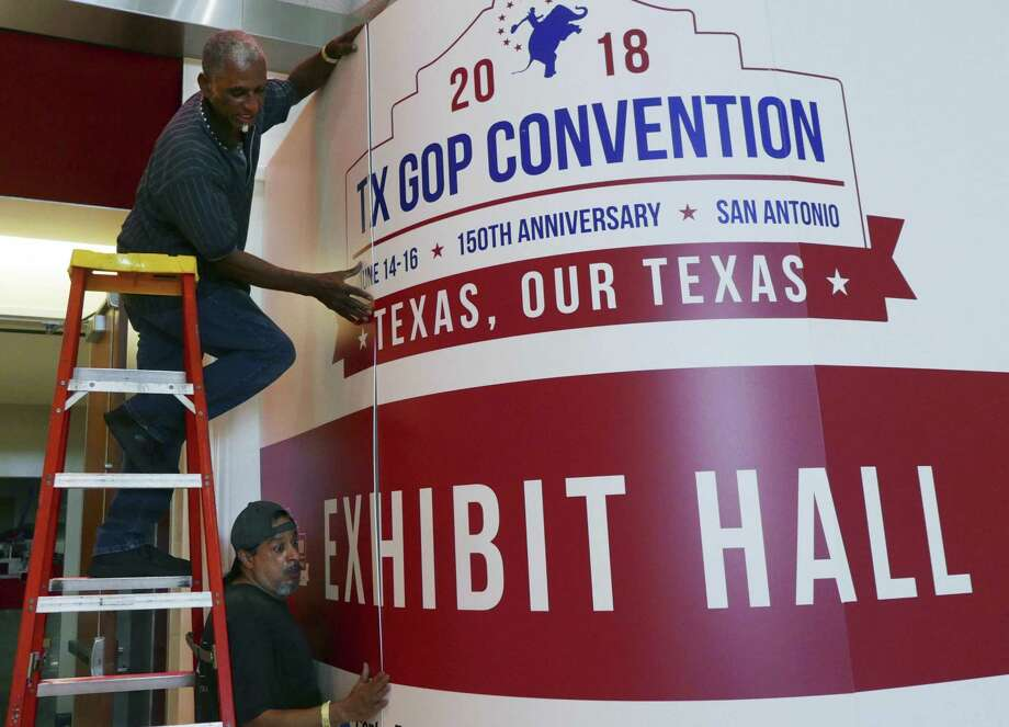 Howard Satterwhite top, and Leonard Jimenez install a sign at the entrance to the convention hall in preparation for the opening of Republican Party of Texas state convention at the Henry B. Gonzalez convention center. The convention runs from June 14 through June 16. Photo: Billy Calzada, Staff / San Antonio Express-News