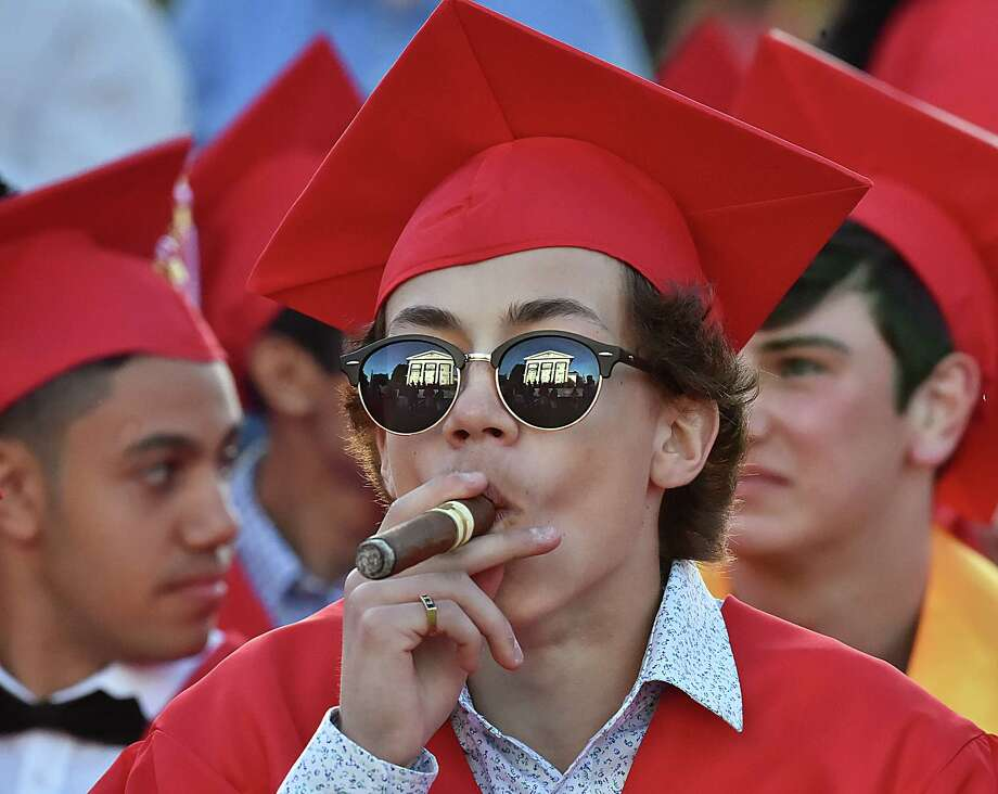 The Branford Town Hall is reflected in the sunglasses of Pasquale Candela who is smoking a cigar after the class of 2018 received their diplomas at Branford High School graduation, Tuesday, June 12, at the Branford Green. Photo: Catherine Avalone, Hearst Connecticut Media / New Haven Register