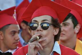 The Branford Town Hall is reflected in the sunglasses of Pasquale Candela who is smoking a cigar after the class of 2018 received their diplomas at Branford High School graduation, Tuesday, June 12, at the Branford Green.