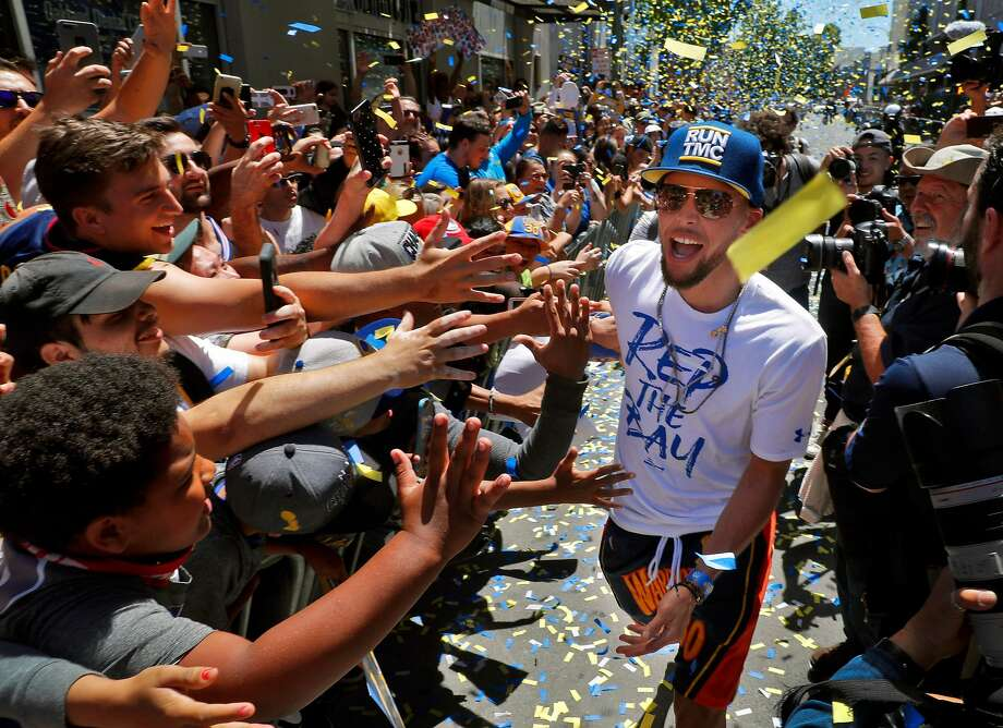 Stephen Curry rushes by high fiving fans behind barriers during the Golden State Warriors NBA Championship parade in Oakland, Calif., on Tuesday, June 12, 2018. Photo: Carlos Avila Gonzalez / The Chronicle