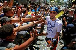 Stephen Curry rushes by high fiving fans behind barriers during the Golden State Warriors NBA Championship parade in Oakland, Calif., on Tuesday, June 12, 2018.