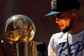 Stephen Curry holds the Larry O'Brien trophy during Golden State Warriors' NBA Championship parade in Oakland, CA on Tuesday, June12, 2018.