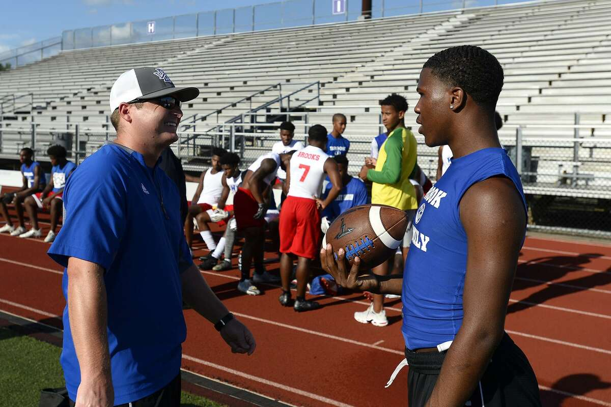 West Brook assistant coach Kurt Zihlman talks with quarterback L'Ravien Elia during a break in a 7-on-7 football game against Port Neches-Groves at Indian Stadium. Photo taken Tuesday 6/12/18 Ryan Pelham/The Enterprise