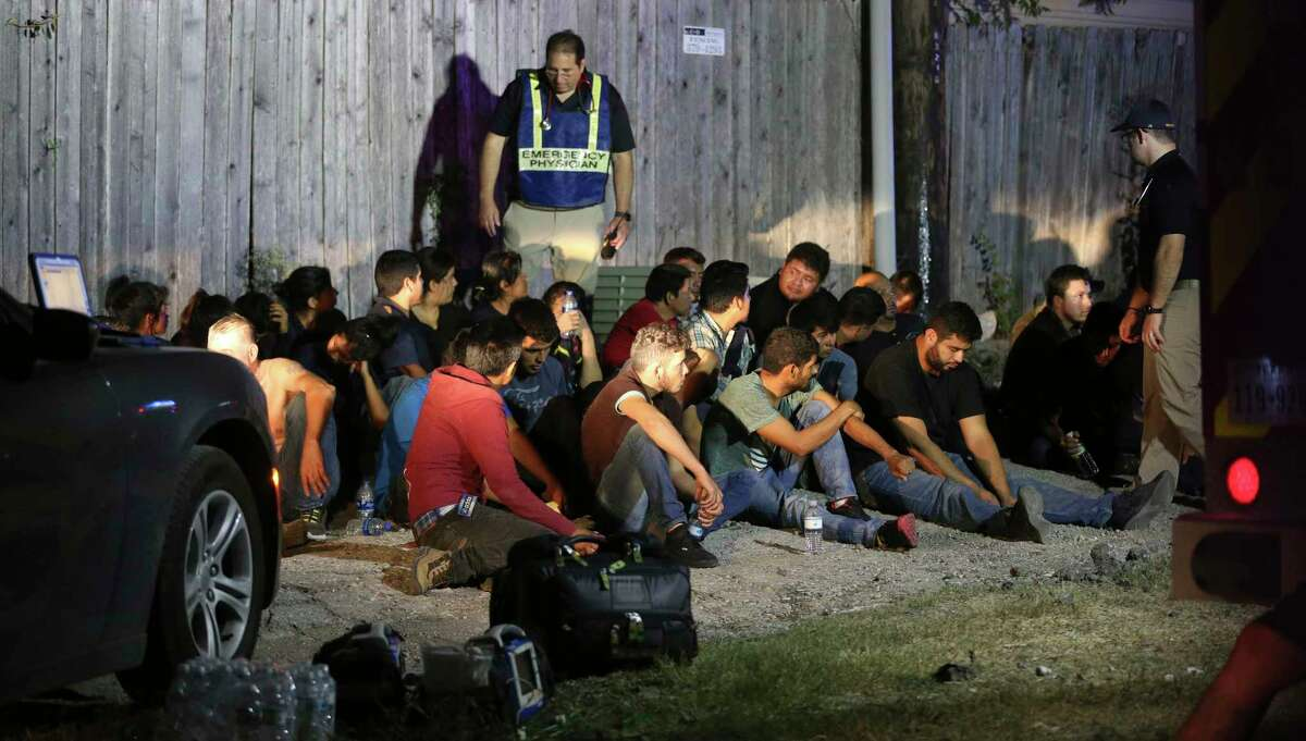 People believed to be undocumented immigrants sit on the ground Tuesday night, June 12, 2018 after being found in the back of an 18-wheel truck near loop 410 and Broadway in San Antonio.