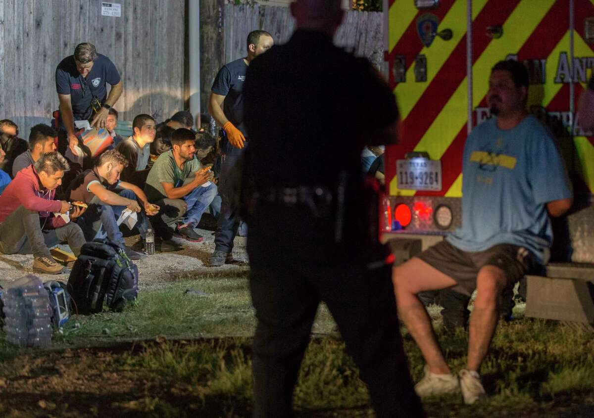 A man in handcuffs is watched by a police officer as people believed to be undocumented immigrants sit on the ground Tuesday night, June 12, 2018 after being found in the back of an 18-wheel truck near loop 410 and Broadway in San Antonio.