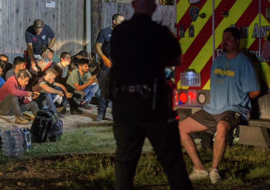 A man in handcuffs is watched by a police officer as apparently undocumented immigrants sit on the ground Tuesday night, June 12, 2018 after being found in the back of an 18-wheel truck near loop 410 and Broadway. Photo: William Luther, San Antonio Express-News / © 2018 San Antonio Express-News
