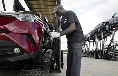 Driver John Massenburg secures Toyota vehicles to a car hauler to take to dealerships at the Gulf States Toyota vehicle processing facility Wednesday, May 23, 2018, in Houston, TX. The facility averages around 6000 Toyota vehicles on the lot at anytime being prepped and processed before being sent to Toyota dealerships. (Michael Wyke / For the  Chronicle)