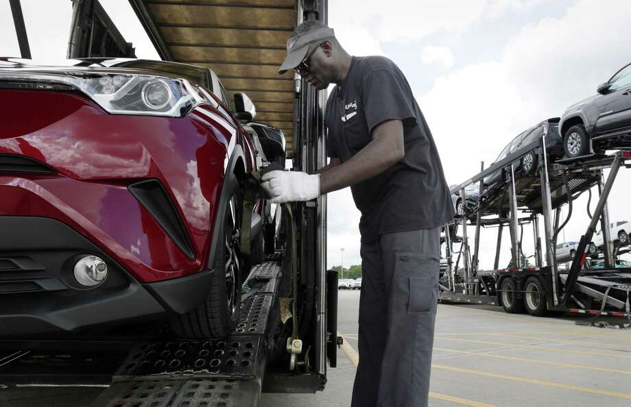 Driver John Massenburg secures Toyota vehicles to a car hauler to take to dealerships at the Gulf States Toyota vehicle processing facility Wednesday, May 23, 2018, in Houston, TX. The facility averages around 6000 Toyota vehicles on the lot at anytime being prepped and processed before being sent to Toyota dealerships. (Michael Wyke / For the  Chronicle) Photo: Michael Wyke, Freelance / For The Chronicle / © 2018 Houston Chronicle