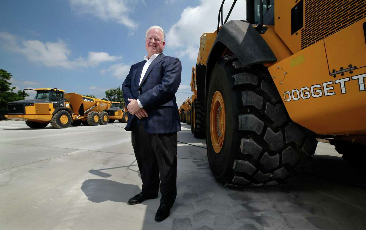 Leslie Doggett, owner of Leslie Doggett Industries, stands beside a row of new articulated dump trucks at the company headquarters on May 18 in Houston.