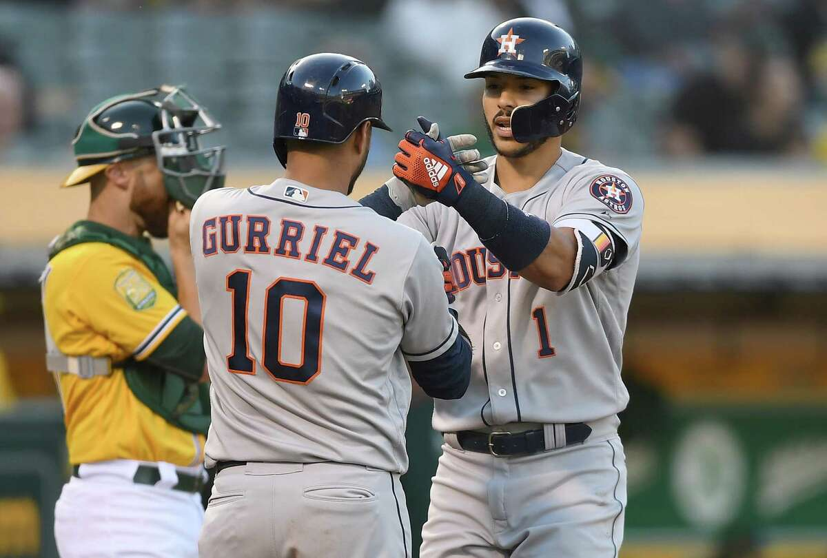 OAKLAND, CA - JUNE 12: Carlos Correa #1 of the Houston Astros is congratulated by Yuli Gurriel #10 after Correa hit a solo home run against the Oakland Athletics in the top of the second inning at the Oakland Alameda Coliseum on June 12, 2018 in Oakland, California.