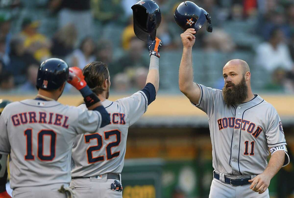 OAKLAND, CA - JUNE 12: Evan Gattis #11 of the Houston Astros is congratulated by Josh Reddick #22 and Yuli Gurriel #10 after Gattis hit a three-run home run against the Oakland Athletics in the top of the second inning at the Oakland Alameda Coliseum on June 12, 2018 in Oakland, California.