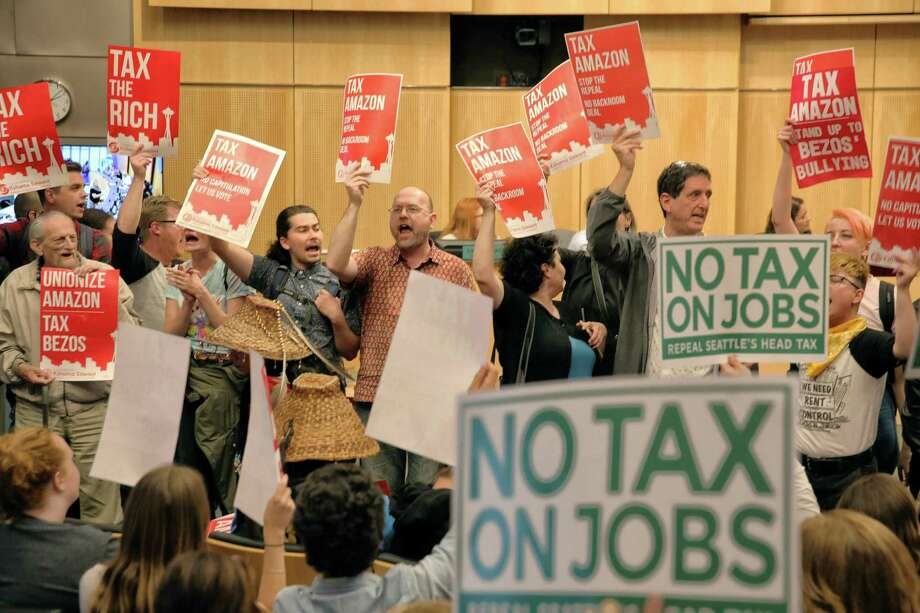 "Supporters and detractors of the ""head tax"" hold signs in council chambers during a City Council vote to repeal the tax on big businesses, which was voted for unanimously last month, Tuesday, June 12, 2018. Council voted 7-2 to repeal the tax. Photo: GENNA MARTIN /SEATTLEPI.COM / SEATTLEPI.COM"