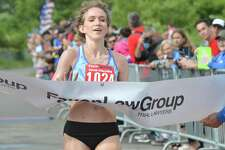 Anna Shields from Harwinton crosses the finish line in first place in the women's division in the Faxon Law Group Fairfield half marathon on June 3.