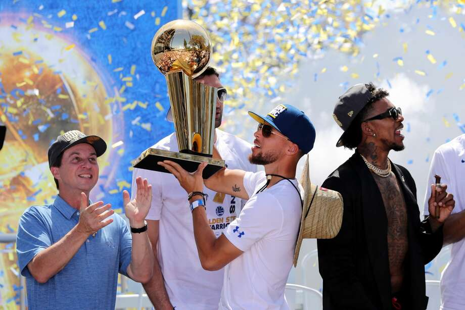 The Golden State Warriors' Stephen Curry holds up the Larry O'Brien NBA Championship Trophy as majorty owner Joe Lacob applauds at the end of the team's championship rally in downtown Oakland, Calif., on Tuesday, June 12, 2018. (Ray Chavez/Bay Area News Group/TNS) Photo: RAY CHAVEZ/TNS