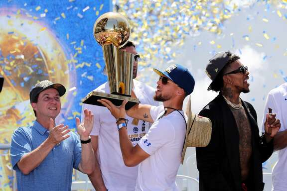 The Golden State Warriors' Stephen Curry holds up the Larry O'Brien NBA Championship Trophy as majorty owner Joe Lacob applauds at the end of the team's championship rally in downtown Oakland, Calif., on Tuesday, June 12, 2018. (Ray Chavez/Bay Area News Group/TNS)