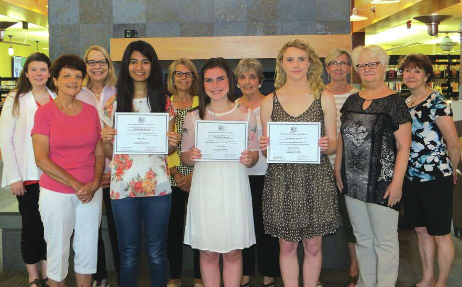 Areej Khan, Sarah Jobe, and Maeve Heumann hold their scholarship awards from the Friends of the Glen Carbon Library with members of the group.