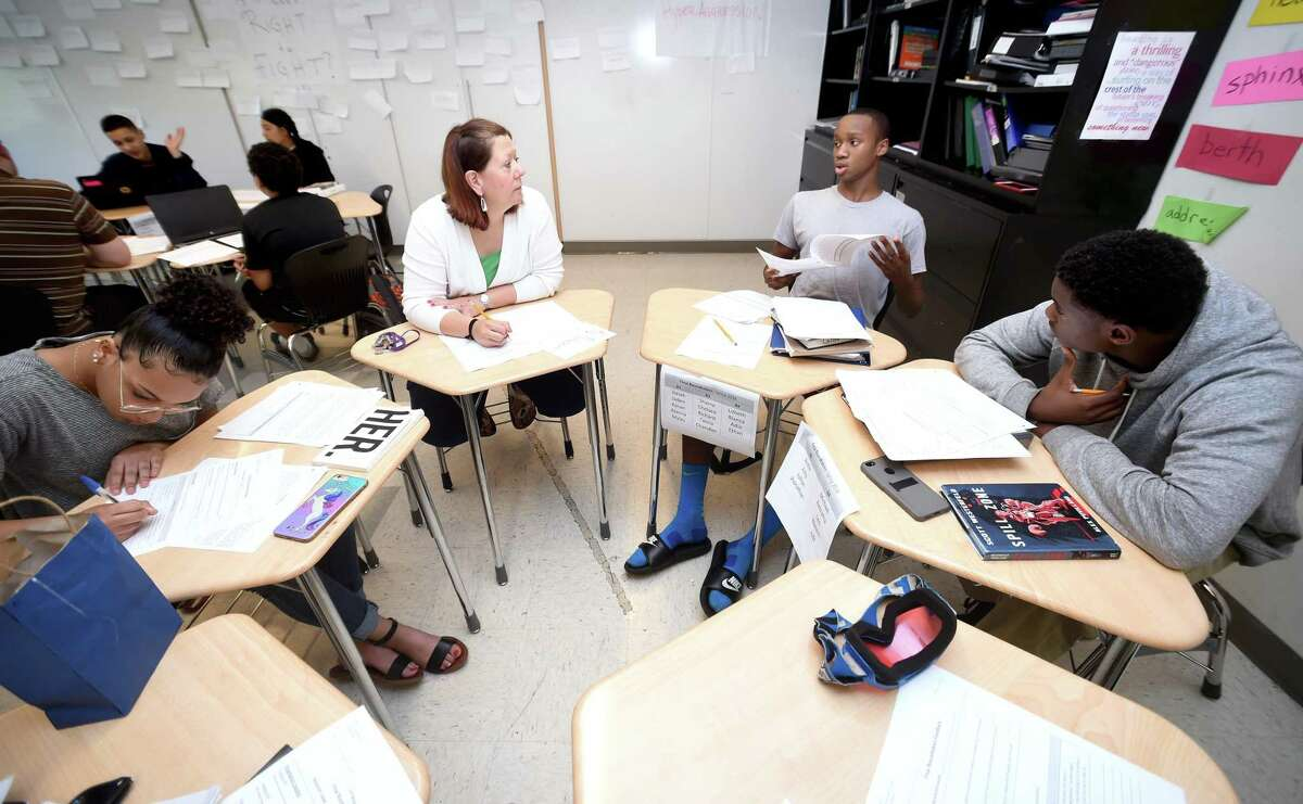 Katie Matheson, center left, listens to Jaden Grant, center right, discuss his project during a final roundtable discussion in his ninth-grade English class at Metropolitan Business Academy in New Haven Tuesday.