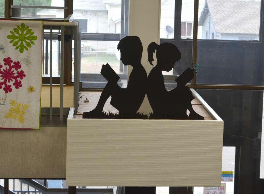 "A silhouette cut out of steel of a boy and girl back-to-back each reading a book has been placed on the transom above the main entrance to Unger Memorial Library as a memorial to longtime patron Susan Yates. In addition, the words ""Welcome to Unger Library"" decorated with butterflies, also cut out of black steel, decorate the area above the checkout desk. Susan McCulloch Yates taught seventh grade English and Art for Plainview ISD and loved reading and butterflies. Before she died at age 85 on Sept. 28, 2017, Yates asked for memorials go to Unger because she felt Plainview's public library ""needed to be dressed up."" The memorial donations were used to commission the steel artwork which were crafted by Brundage Manufacturing in Plainview. The silhouette of the young readers have replaced a mosaic sculpture of a mermaid created many years ago by Candace Keller for a theatrical performance at Wayland Baptist University. The sculpture was retired after pieces of glass forming the mosaic began falling each time the artwork was dusted. Photo: Doug McDonough/Plainview Herald"