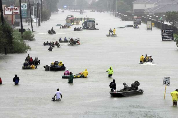 Rescue boats fill a flooded street as flood victims of Hurricane Harvey are evacuated in Aug. 2017.