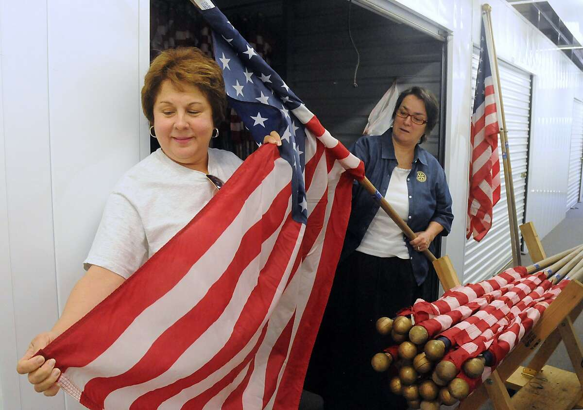 Kngwood Rotary Club members Carolyn Wise and Tommie Buscemi of American Flags examine the American Flags inside their storage unit. The Kingwood Rotary Club places the American Flag at residents and businesses, that have subscribed to the Rotary Club, during certain holidays. Photo by David Hopper