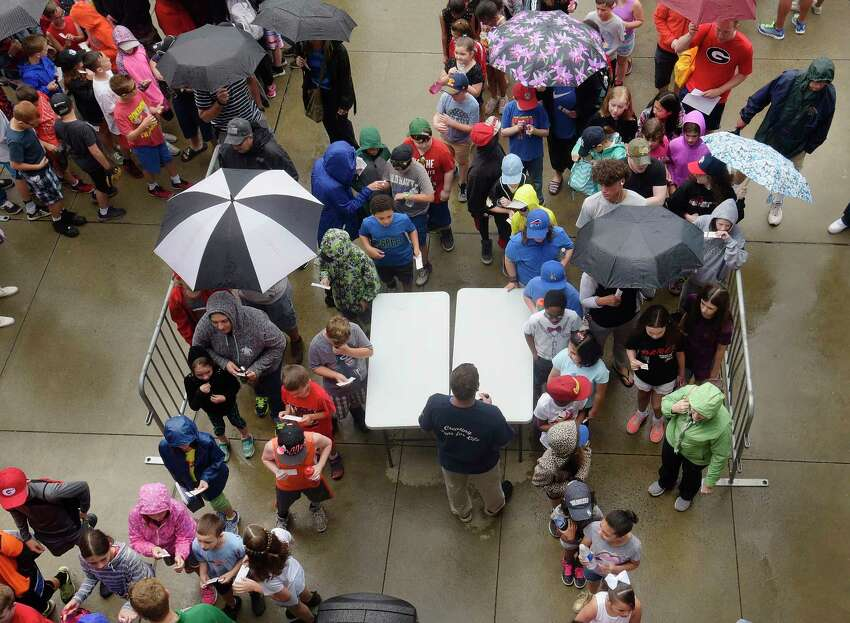 Area school children and some adults make their way into Joe Bruno Stadium in the rain for an exhibition baseball game between the Tri-City ValleyCats and the Albany Dutchmen on Wednesday, June 13, 2018, in Troy, N.Y. (Paul Buckowski/Times Union)