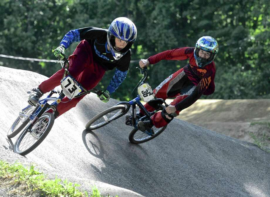 Travis Cortis, 13, left, and his brother Dakota, 17, of Ware, MA, make their way through one of the banked curves on the Bethel Supercross BMX track. The track, in association with USA BMX and the US Olympic Committee, hosted an Olympic Day Race on Wednesday, June 22,2016. The race was free for riders and spectators with the goal to promote BMX racing which is an Olympic sport and will be featured at the 2016 Summer Olympic in Rio. Travis and Dakota came to the event with their siblings Daniel, 23, Kyle, 18, Kaylynn, 15, Shyane, 12, and Savanna, 11, who were all there to race. Photo: H John Voorhees III / Hearst Connecticut Media / The News-Times