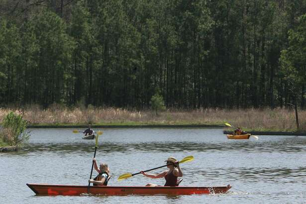 Kayakers enjoy a sunny day on Lake Woodlands during an afternoon kayaking adventure. Single kayaks are rented out at $15 per hour and tandem kayaks at $20 per hour with an additional $5 per hour.